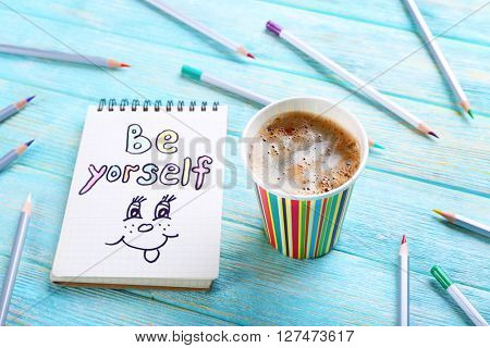 Cup of coffee with crayons and note BE YOURSELF on wooden background