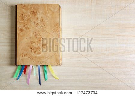 Brown notebook with bookmarks on wooden table