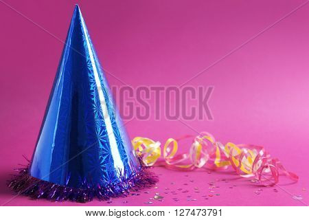 Funny party hat on purple background