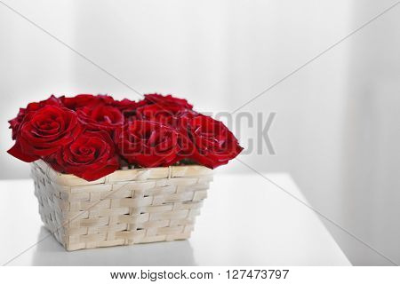 Red roses in basket on a table