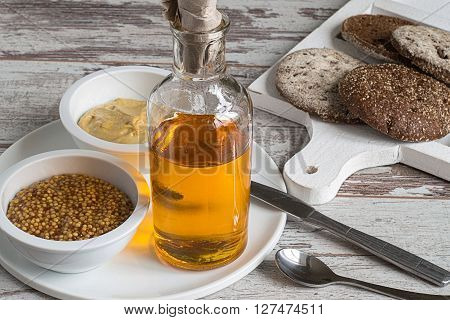 Bottle with mustard oil, two cups with mustard and a cutting board with bread on a light wooden background.