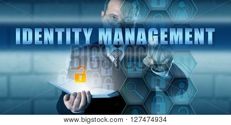 Manager pushing IDENTITY MANAGEMENT on a virtual interactive touch screen interface. Information technology security concept for managing the identification of individuals hardware and application.