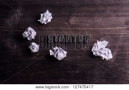 Office desk with start up sign made of cookie cutters and crumpled paper balls. Flat lay. Workplace. Studio shot on wooden background.