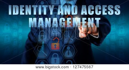 Business manager is touching IDENTITY AND ACCESS MANAGEMENT on an interactive visual screen. Information technology security concept for management of access rights identification processes.