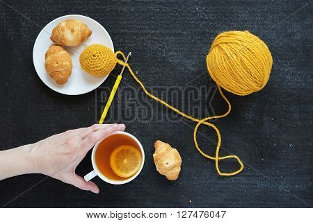 Lemon tea, yellow crocheting and croissants on a plate. Female hand is taking a cup of tea.