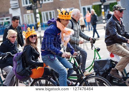 AMSTERDAM, NETHERLANDS on APRIL 26, 2015. City natives and tourists on bike with crown decoration celebrating Queen's Day or King's day, Dutch annual national holiday, in Amsterdam streets, Holland