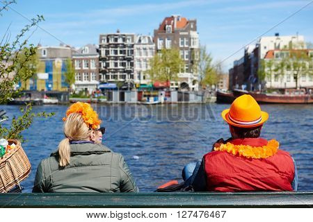 AMSTERDAM, NETHERLANDS on APRIL 26, 2015. City natives and tourists with orange color decoration watching celebrating Queen's Day or King's day, Dutch annual national holiday, in Amsterdam, Holland