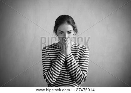 Sad woman in a sailor's striped vest covering her mouth with hands. Retouched image. Vignette is added.