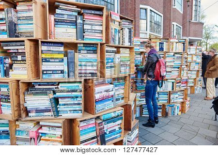 AMSTERDAM, NETHERLANDS on APRIL 26, 2015. Flea book market for natives and tourists during Queen's Day or King's day, Dutch annual national holiday, in the street of in Amsterdam, Holland