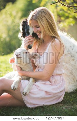 Young blonde woman outdoor portrait with lamb and russian wolfhound dog. Life at the farm.
