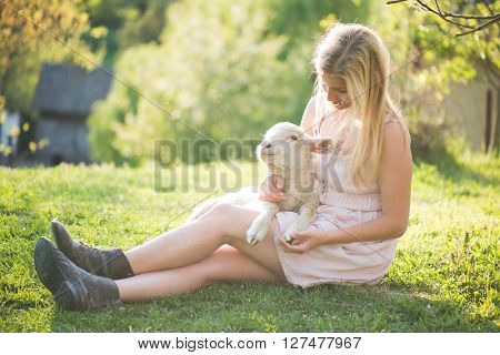 Farmer woman posing outdoor with cute baby lamb. Cute young lamb at her legs. Woman legs in old leather boots.