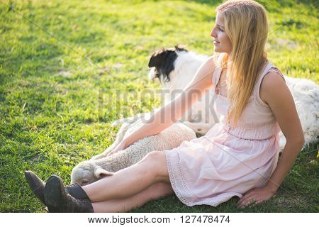 Farmer woman posing outdoor with cute baby lamb. Cute young lamb at her legs. Woman legs in old leather boots. Summer portrait.