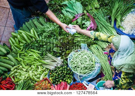 The seller gives the money to the buyer at the vegetable market