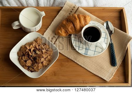 Healthy breakfast in the morning served on tray in bed with coffee, cornflakes, croissant and milk