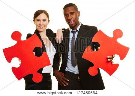 Smiling business people holding two red jigsaw puzzle pieces