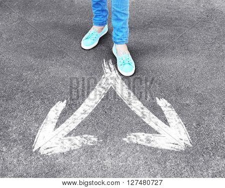 Female feet standing on road with white arrows