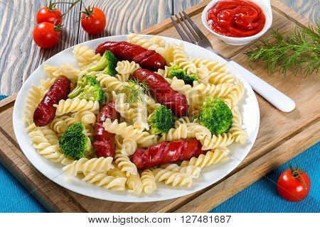 Delicious Spiral Pasta salad with broccoli and grilled sausages decorated with dill on a white dish with tomato sauce in a gravy boat and fork on a cutting board studio lights close-up