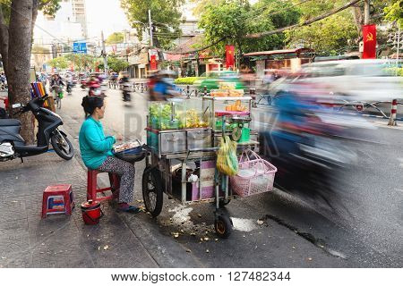HO CHI MINH VILLE, VIETNAM, FEBRUARY 22, 2015 : Long time exposure on a fruit seller on the sidewalk along the road in the district 1 of Ho Chi Minh Ville, (Saigon), Vietnam.