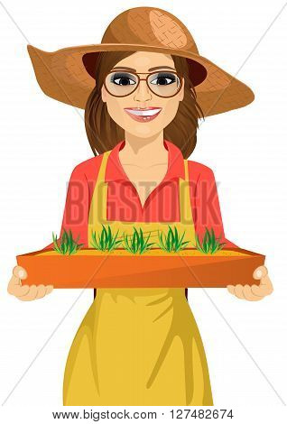 Young brunette farmer woman with glasses holding a box of fresh green seedlings plants