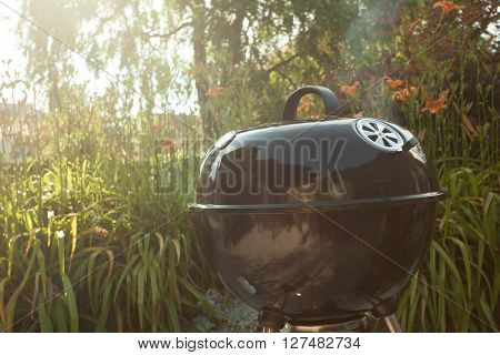 BBQ grill standing on a backyard on a hot sunny day