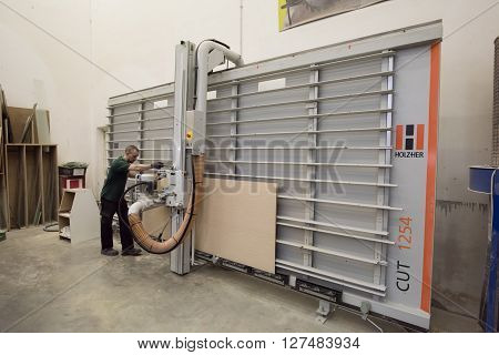 Saint-Petersburg Russia - April 26 2016: Worker cuts the size of the wood particle board on woodworking machines Holzher in the store building materials.
