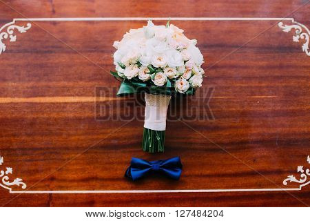 Bouquet from a pink rose and blue bow-tie.