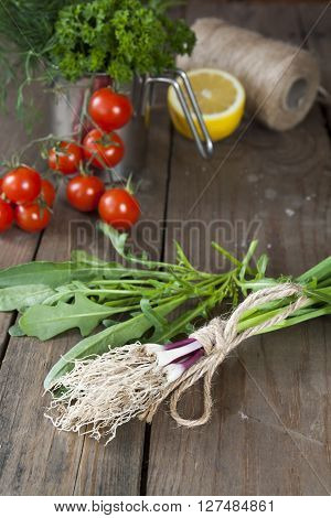 Fresh Green Garlic Spears And Arugula On Wooden Table With Tomatoes And Lemon