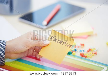 Human hand holding adhesive note with Vacation text