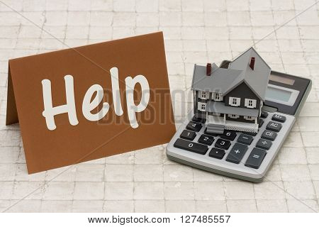 Help with Your Mortgage A gray house brown card and calculator on stone background with text Help
