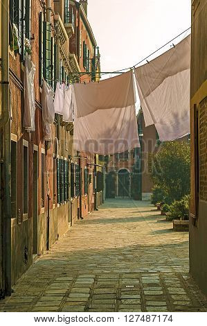 BURANO, ITALY - JANUARY 25, 2016: Laundry out to dry in a courtyard between houses Burano Italy. Typically Italian. Morning light.