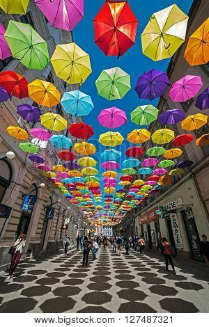 TIMISOARA ROMANIA - APRIL 22 2016: Street with colored umbrellas and shadows in Timisoara Romania