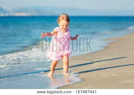 Little girl playing on beautiful ocean beach