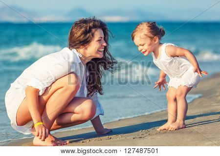 Mother and little daughter playing on the beach