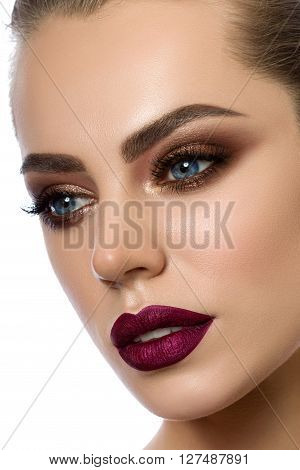 Close-up portrait of young woman with wine red lips and bronze smokey eyes. Modern fashion make-up. Studio shot