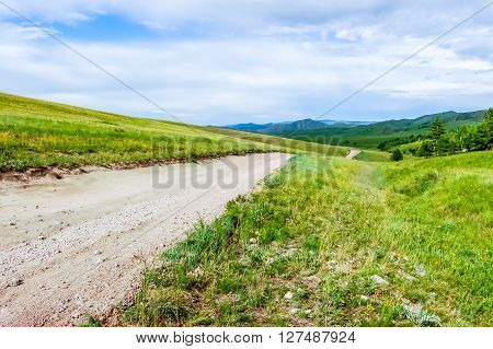 Dirt road through lush rolling hills of Central Mongolian steppe