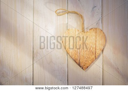Wooden heart in the sun on a bright wooden background.
