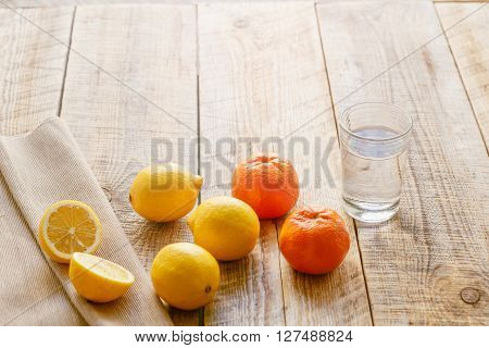 composition of lemons, oranges and glass of water, and piece of cloth on a wooden table