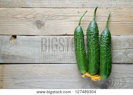 Cucumbers on old wooden background top view