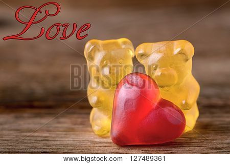 macro two yellow gummy bears with red hearts and writing love on wood