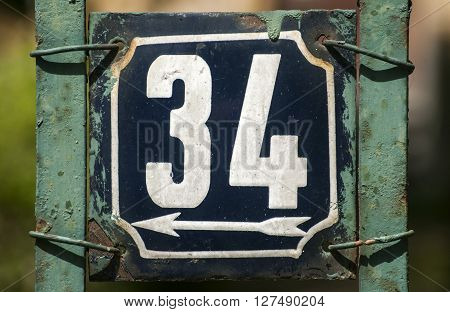Old retro weathered cast iron plate with number 34