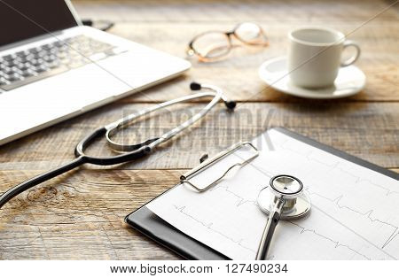 doctor workplace with a stethoscope and laptop, glasses and coffe cup at wooden table