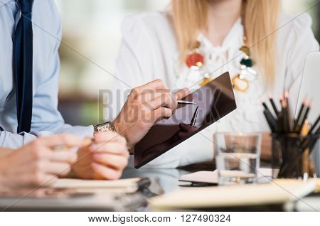 Closeup of a business man using digital tablet in a meeting to discuss future plans. Close up of a man hand pointing on tablet. Closeup of male hand showing business project on digital tablet.