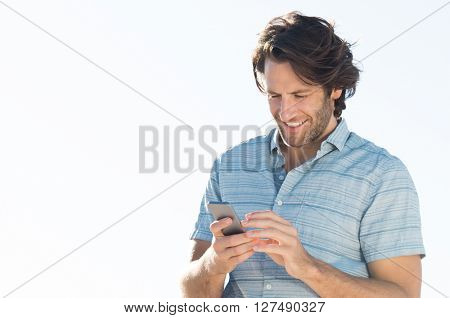 Handsome young man checking emails on his smart phone. Young man smiling and reading a phone message outdoor. Young man in casual using telephone, copy space.