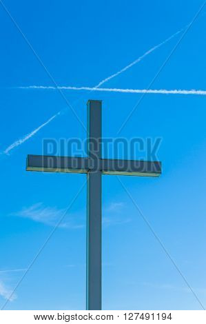 Detail of a religious cross while a cross is designed into the sky by a trail of two airplanes