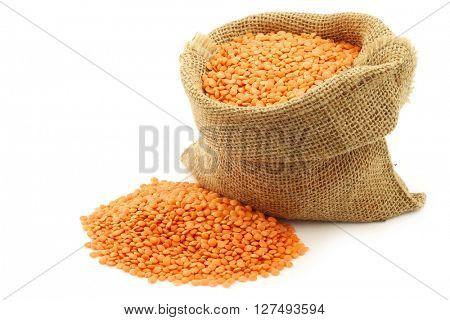 red lentils in a burlap bag on a white background