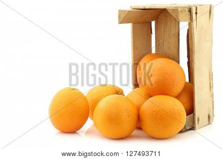 fresh oranges in a wooden crate on a white background