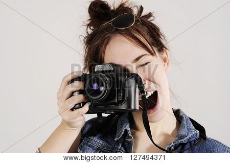 Funny young girl with photo camera with moving, blowing hair.