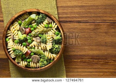 Pasta primavera with green asparagus pea broccoli mushroom and tomato in cream sauce served in wooden bowl photographed overhead on dark wood with natural light