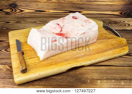 Piece of fresh raw pork lard and knife on wooden board rustic background