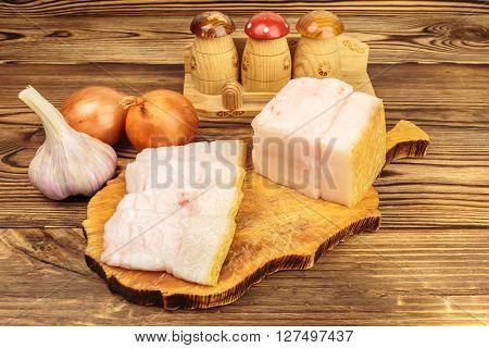 Piece and sliced fresh raw pork lard on wooden board garlic onion on the table